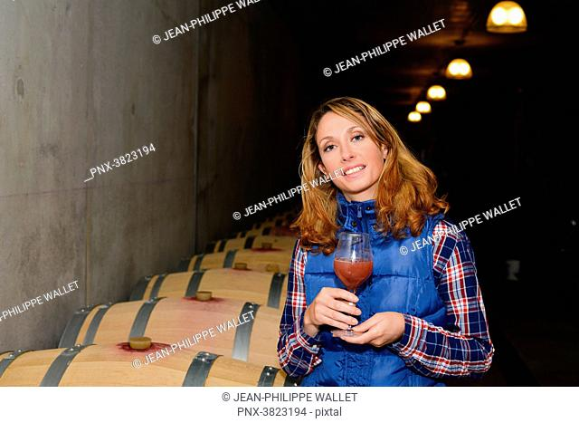 cheerful young woman oenologist tasting a glass of wine in cellar with wine barrel in background- Cepage Grenache, Chateauneuf du Pape, cotes du Rhone, France
