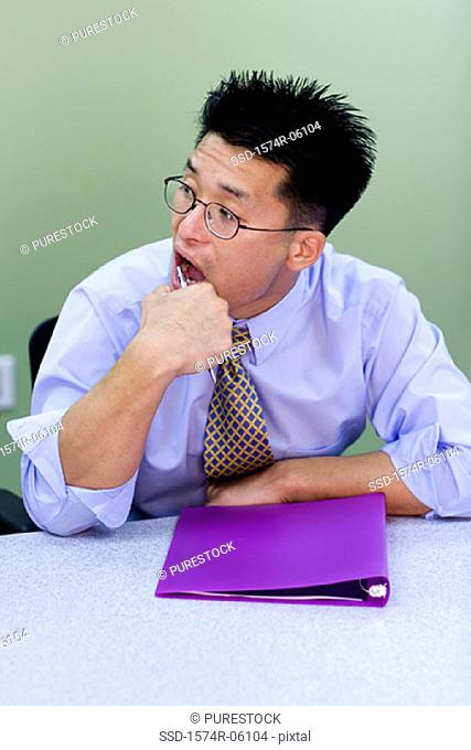 Businessman sitting in an office with a file in front of him