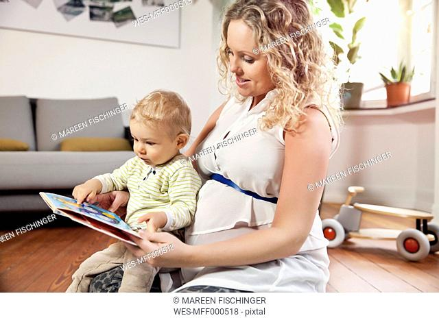 Germany, Bonn, Pregnant mother reading book to son in living room