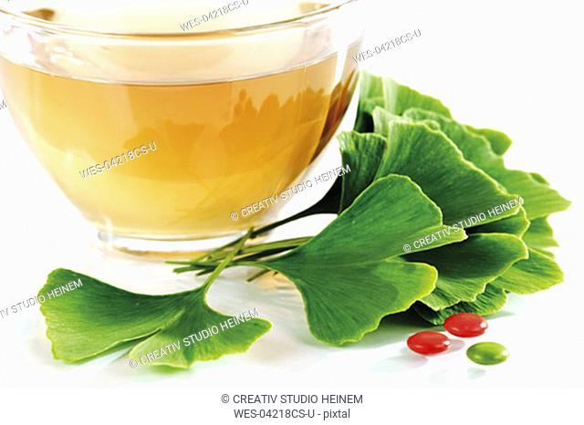 Ginko tea in cup with leaves and tablets