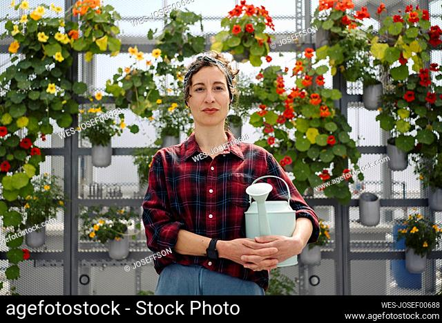 Portrait of woman holding watering can in front of flowers in a gardening shop