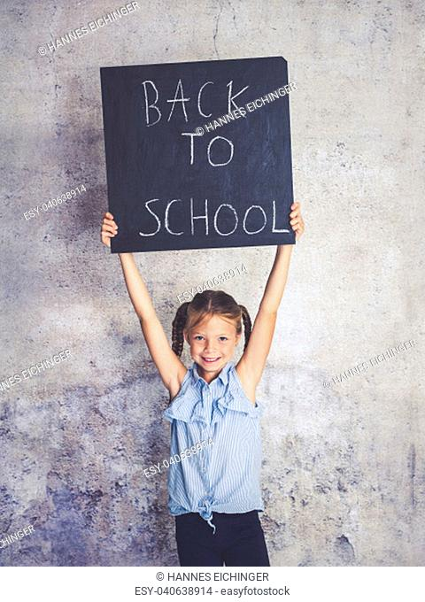 schoolgirl is holding blackboard with the words back to school in front of concrete background