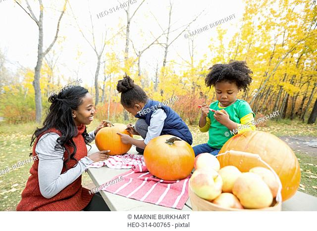 Mother and daughters carving pumpkins on picnic table in autumn park