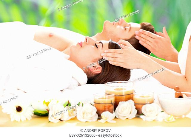 Side view of relaxed young couple receiving head massage at beauty spa
