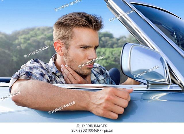 Man checking himself in car side mirror