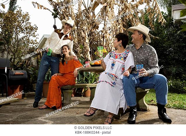 Portrait of a cheerful Tex-Mex family sitting together in the backyard of house