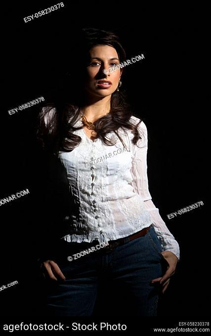 A beautiful brunette model posing in a studio environment