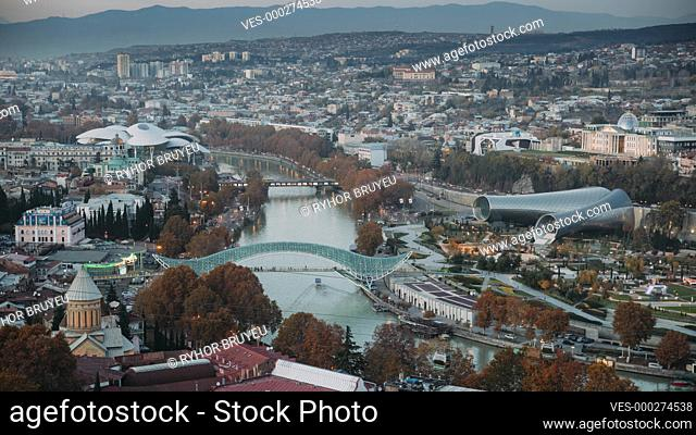Tbilisi, Georgia. Top View Of Famous Landmarks In Autumn Evening. Georgian Capital Skyline Cityscape. Bridge Of Peace, Concert Hall, Rike Park