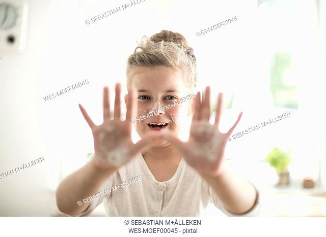 Portrait of smiling girl in the kitchen with dough on hands and face