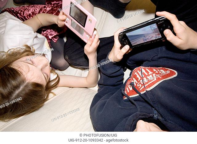 Children playing games on handheld consoles UK