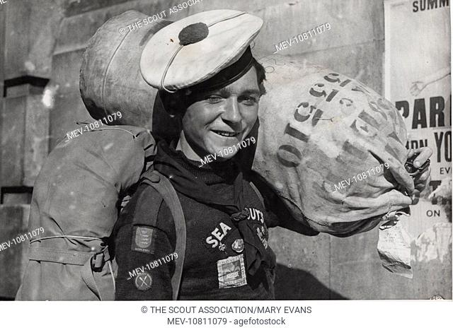 English sea scout returning home from the World Jamboree, wearing a French sea scout's beret. He is Trevor Thomas of Staines, Middlesex