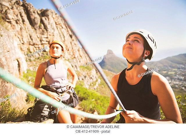 Female rock climber holding ropes