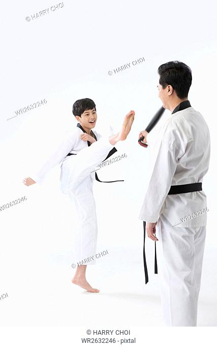 Side view of smiling father and son in Taekwondo uniforms practicing