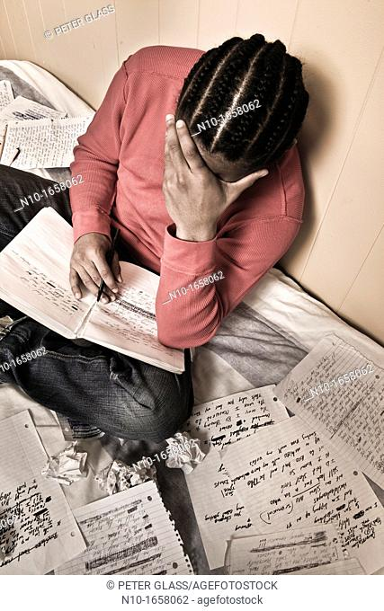 Young black man writing in his notebook