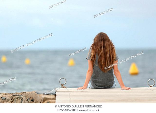 Back view portrait of a lonely teen looking at the ocean