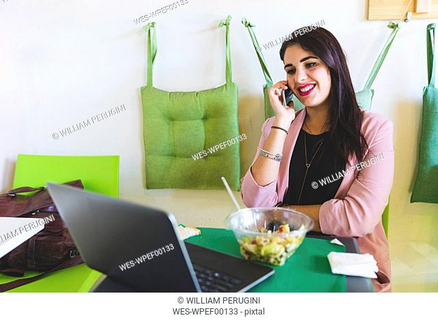 Young businesswoman having healthy lunch using cell phone and laptop