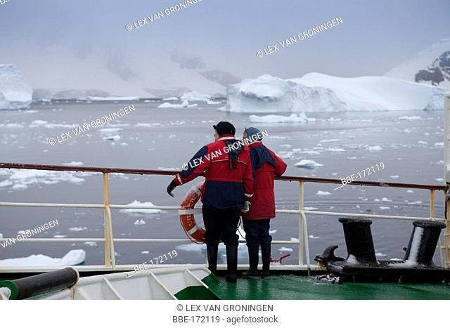 Couple on board the cruise ship Antarctic Dream gazing at the scenery offered by the Errera Channel, off Danco Island, Antarctic Peninsula