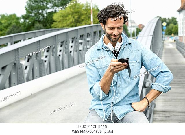 Smiling man on a bridge looking at cell phone