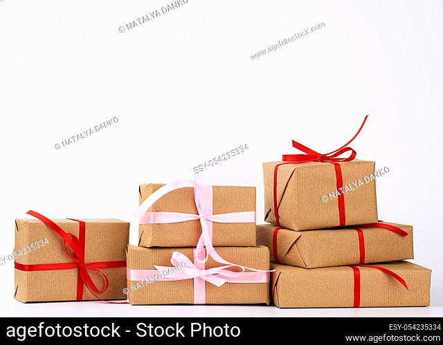 stack of gifts in boxes wrapped in brown kraft paper and tied with silk ribbon on a white background. Festive concept, copy space