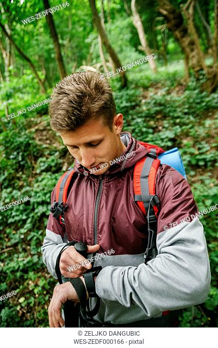 Serbia, Rakovac, young hiker looking at smartwatch