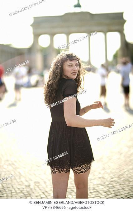 young woman walking towards Brandenburg Gate in Berlin, Germany