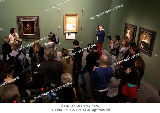 """07 March 2019, Baden-Wuerttemberg, Stuttgart: Visitors stand in front of the shredded Banksy picture """"""""Love is in the Bin"""""""" (M) in the State Gallery"""