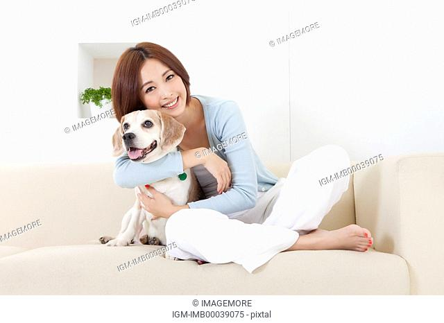Young woman sitting on the sofa with her dog and smiling at the camera