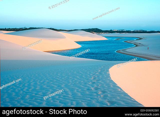 Lagoons in the desert of Lencois Maranhenses National Park, Brazil, low, flat, flooded land, overlaid with large, discrete sand dunes with blue and green...