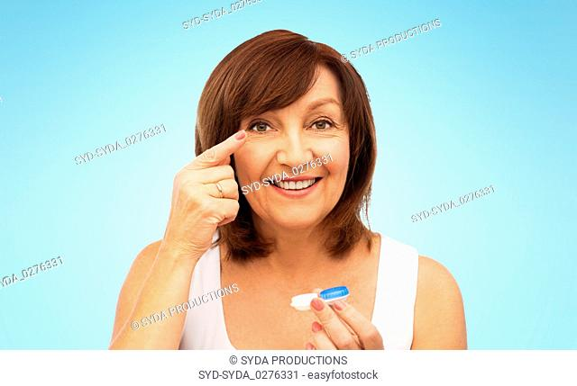 happy senior woman applying contact lenses