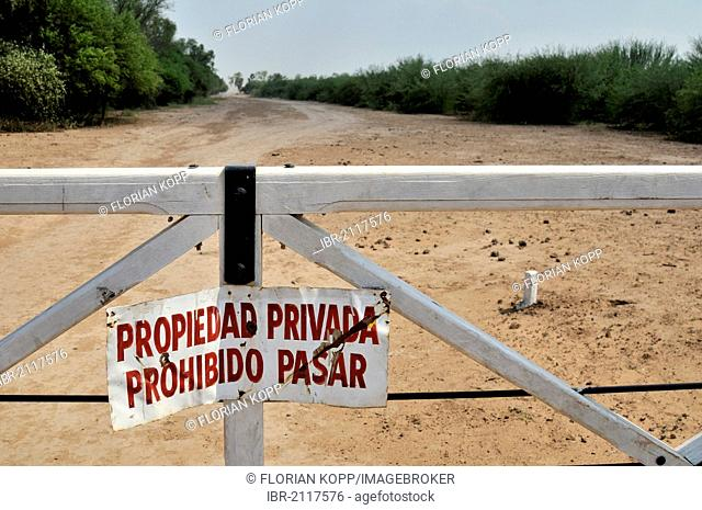 Sign on a gate Propiedad privada, Prohibido pasar, private property, access prohibited, marking the grounds of a major landowner in the Gran Chaco region