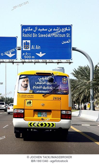 School bus displaying the picture of Muhammad bin Rashid Al Maktoum, the ruler of the Emirate of Dubai, bus driving on a motorway in Abu Dhabi