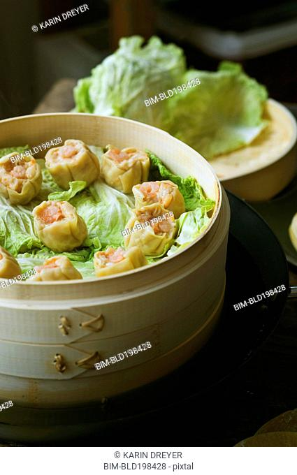 Asian dumplings in steamer with cabbage