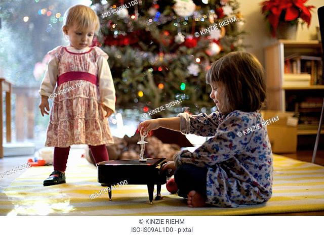Two young sisters listening to toy piano music box at Xmas