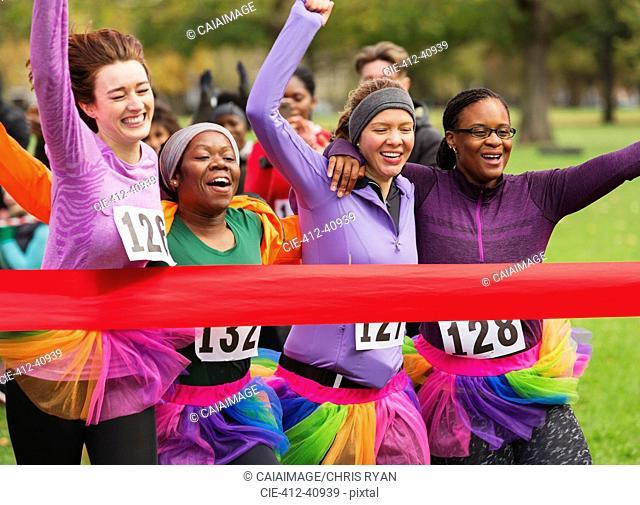 Women friend runners in tutus running, crossing charity run finish line