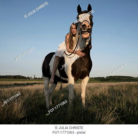 Portrait girl laying on horse in rural field