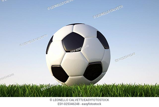 Soccer ball close up on grass lawn. Viewed from ground level. In sunny day light. . With blue sky and no clouds as background. Clipping path included