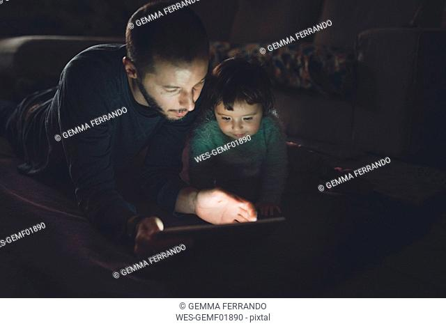 Father and daughter looking at digital tablet at home in the dark