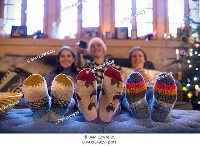 Family with colorful socks relaxing, watching TV in living room