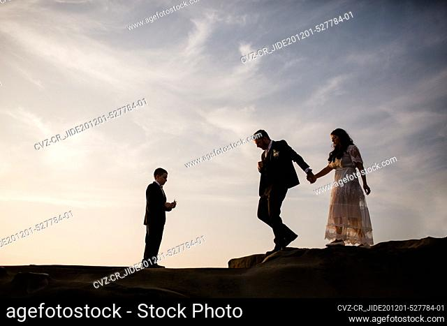 Newlyweds & Nine Year Old Son Standing on Rock at Beach in San Diego