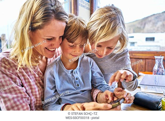 Happy mother with two sons sitting at table in a cafe playing with cell phone