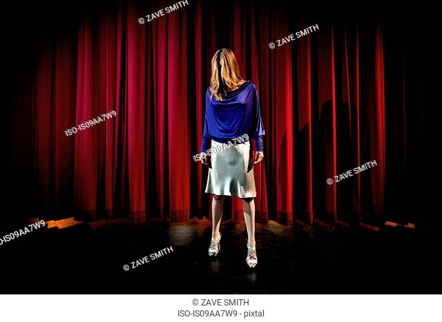Mature woman standing in theatre stage with hair covering face