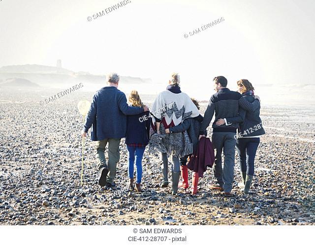 Multi-generation family walking in a row on beach