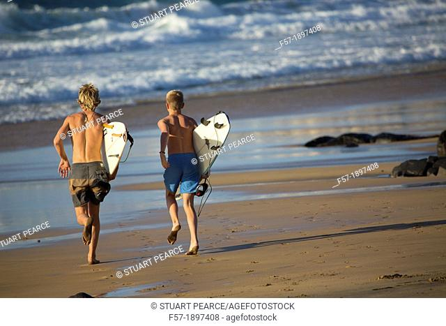 Two young surfers on El Cotillo beach in Fuerteventura, Spain