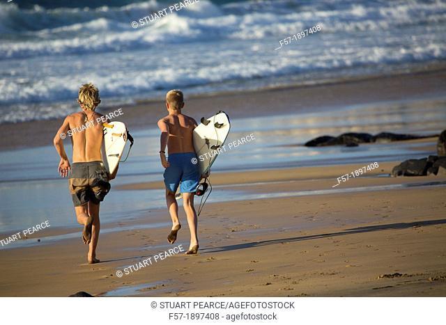 Two young surfers on El Cotillo beach in Fuerteventura, Spain
