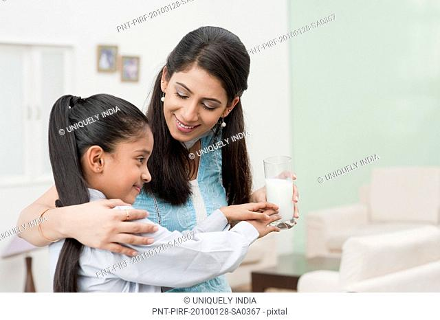 Woman giving a glass of milk to her daughter
