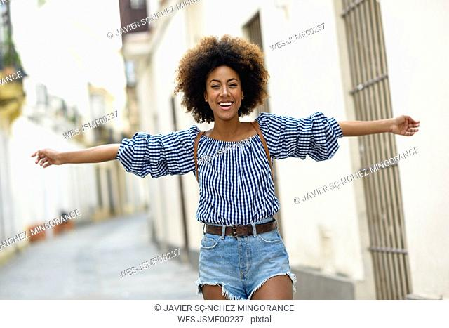 Portrait of happy young woman with curly brown hair on the street