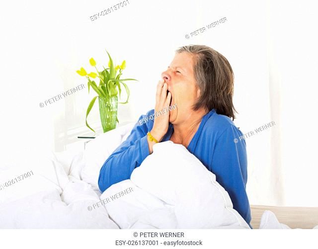 woman in her fifties sitting in her bed and waking up