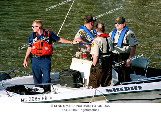 Law authorities patrol river during night festival prior to Port Huron to Mackinac sailboat race. Michigan. USA