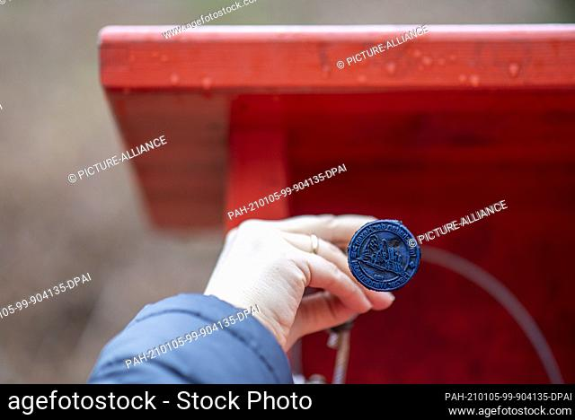 """31 December 2020, Saxony-Anhalt, Halberstadt: A hiker holds a stamp for the """"""""Harzer Wandernadel"""""""" (Harz Hiking Needle) in his hand at a stamping point at the..."""