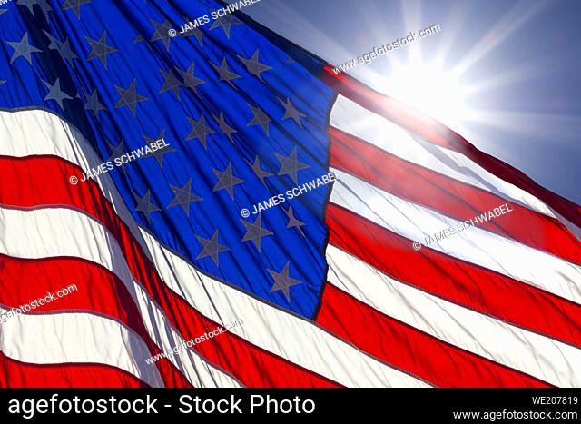 Sunburst behind America flag in blue sky